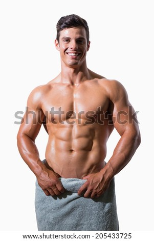 Portrait of a smiling shirtless muscular man wrapped in white towel over white background - stock photo