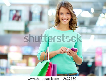 Portrait of a smiling shopper sending a text message - stock photo