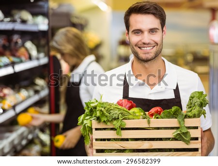 Portrait of a smiling staff man holding a box of fresh vegetables at supermarket - stock photo