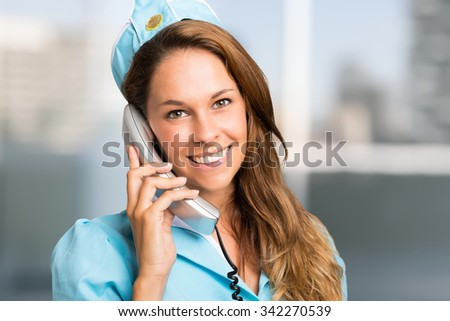 Portrait of a smiling stewardess talking on the phone - stock photo