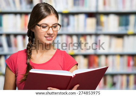 Portrait of a smiling student in a library - stock photo