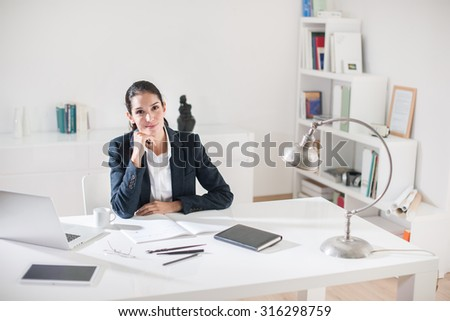 Portrait of a smiling successful middle age businesswoman with dark hair sitting at her white desk in her office She is wearing a black suit jacket, holding her chin, her laptop and coffee next to her
