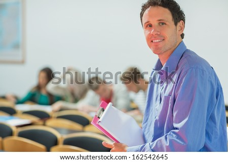Portrait of a smiling teacher with young college students in the classroom - stock photo