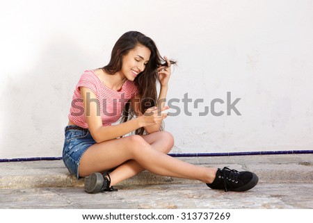 Portrait of a smiling teen sitting outside looking at mobile phone