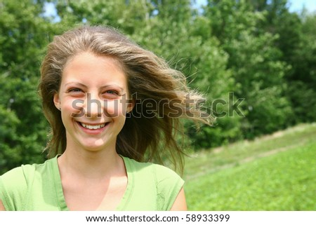 portrait of a smiling teenager girl in a green meadow - stock photo