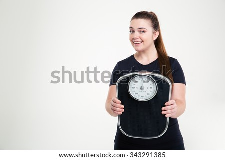 Portrait of a smiling thick woman holding weighing machine isolated on a white background - stock photo