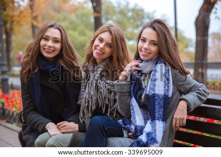 Portrait of a smiling three girlfriends sitting on the bench outdoors