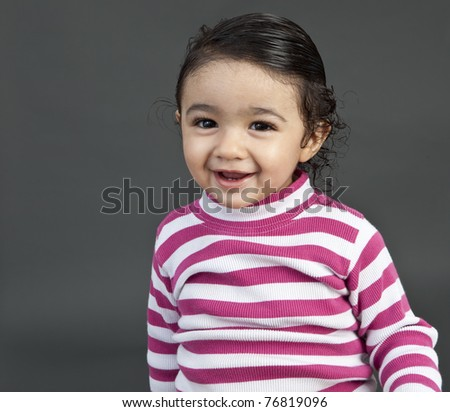 Portrait of a Smiling Toddler Girl on a Grey Background - stock photo