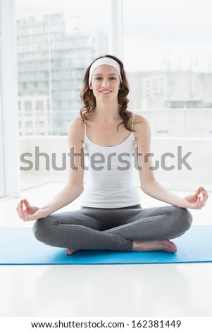Portrait of a smiling toned young woman sitting in lotus pose at fitness studio