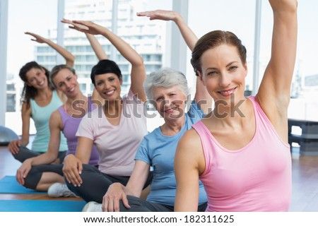 Portrait of a smiling trainer with women in row stretching hands at yoga class - stock photo
