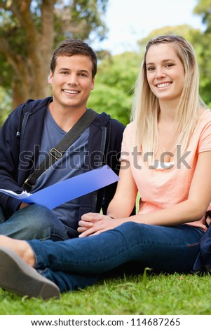 Portrait of a smiling tutor helping a teenager to revise in a park
