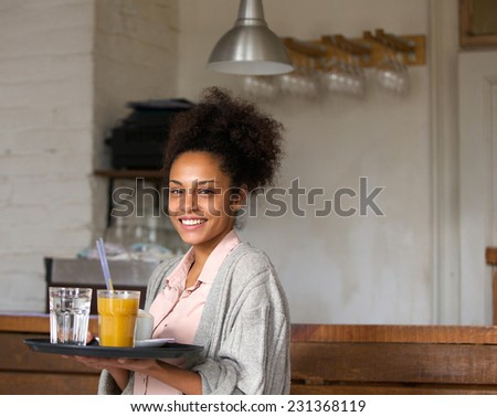Portrait of a smiling waitress holding tray of drinks in restaurant - stock photo