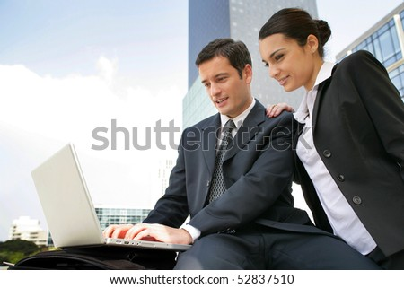 portrait of a smiling woman and a man with a laptop computer - stock photo