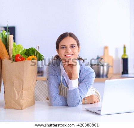 Portrait of a smiling woman cooking in her kitchen sitting - stock photo