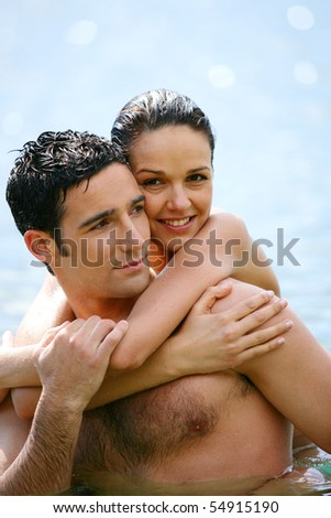 Portrait of a smiling woman embracing a man in the sea - stock photo