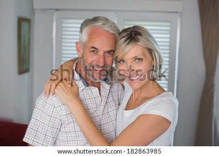 Portrait of a smiling woman embracing mature man at home