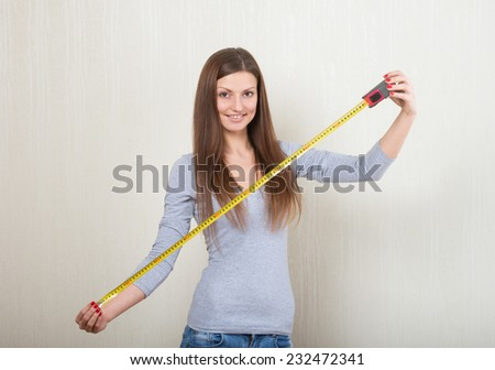 Portrait of a smiling woman extending a tape measure out - stock photo