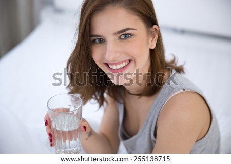 Portrait of a smiling woman holding glass of water - stock photo