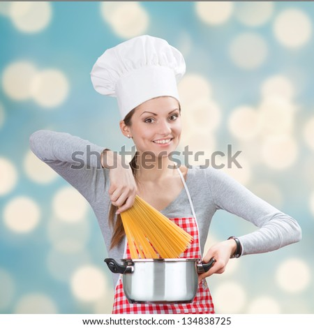 Portrait of a smiling woman in chef's hat adding the pasta to the pot on the blue abstract background - stock photo