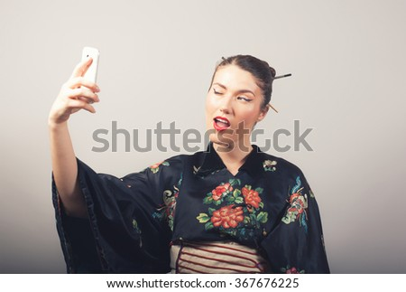 Portrait of a smiling woman in kimono making selfie photo on smartphone - stock photo