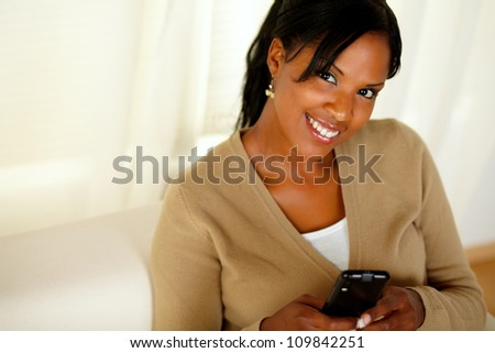 Portrait of a smiling woman looking at you while sending a message with her cellphone - stock photo