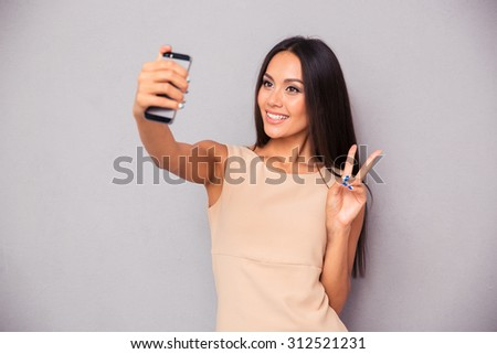 Portrait of a smiling woman making selfie photo on smartphone over gray background - stock photo