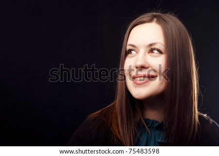 Portrait of a smiling woman on black background. Close-up.