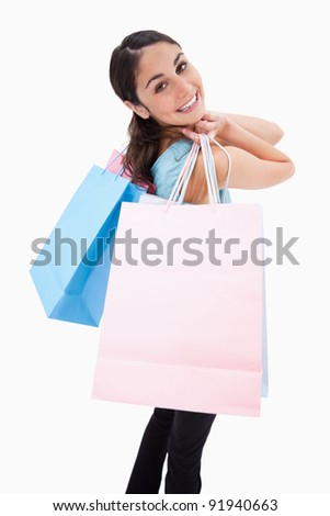 Portrait of a smiling woman posing with shopping bags against a white background