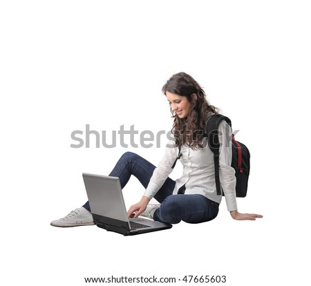 Portrait of a smiling woman sitting and using a laptop - stock photo