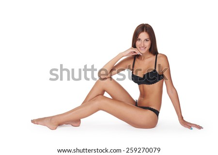 Portrait of a smiling woman sitting down in a studio wearing black lingerie - stock photo