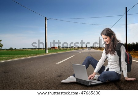 Portrait of a smiling woman sitting on a countryside street and using a laptop - stock photo