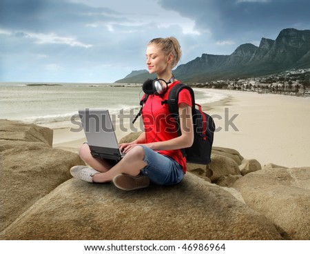 Portrait of a smiling woman sitting on a rock at the seaside and using a laptop - stock photo