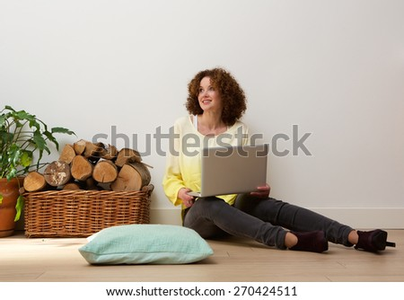Portrait of a smiling woman sitting on floor with laptop at home - stock photo