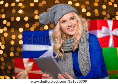 Portrait of a smiling woman using tablet computer with gift boxes on background - stock photo