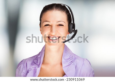 Portrait of a smiling woman wearing an headset - stock photo