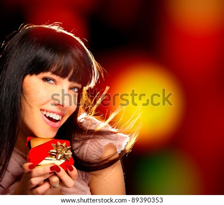 Portrait of a smiling woman with a gift in her hands - stock photo