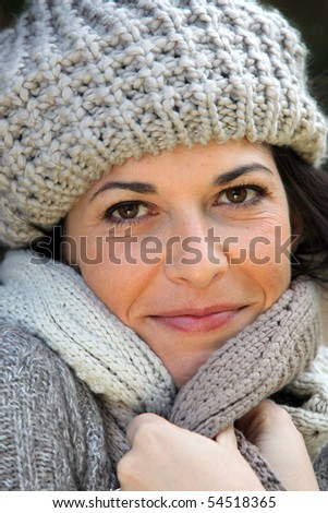 Portrait of a smiling woman with a wool cap - stock photo