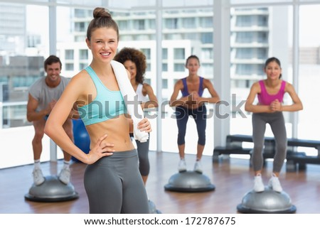 Portrait of a smiling woman with fit people performing step aerobics exercise in gymPortrait of a smiling woman with fit people performing step aerobics exercise in gym - stock photo