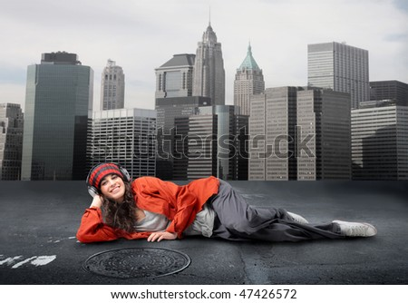 Portrait of a smiling woman with headphones lying in the middle of a city street - stock photo