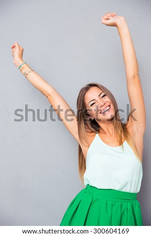 Portrait of a smiling woman with raised hands up over gray background. Looking at camera - stock photo