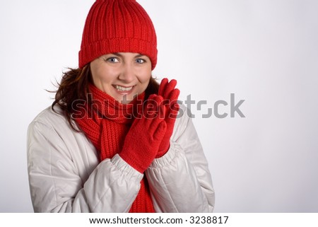 Portrait of a smiling woman with winter outerwear, clapping her gloved hands together. Isolated on white. Horizontal format. - stock photo