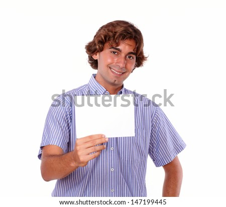 Portrait of a smiling young adult in blue shirt,holding a white blank card on isolated background.