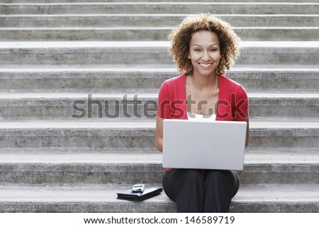 Portrait of a smiling young African American woman using laptop on steps outdoors - stock photo