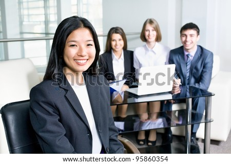 Portrait of a smiling young asian business woman in a meeting - stock photo