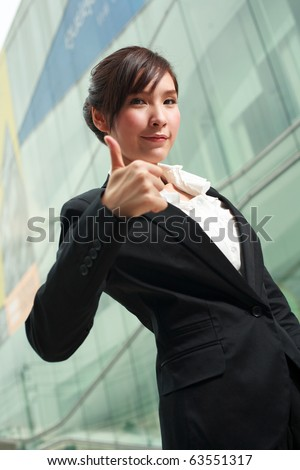 Portrait of a smiling young asian businesswoman showing thumbs up - stock photo
