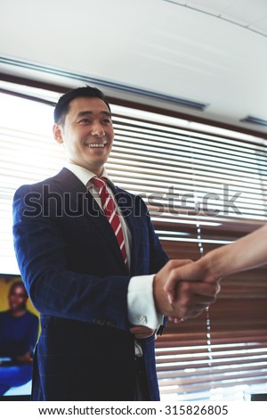 Portrait of a smiling young asian men entrepreneur shaking hands with his work colleagues, successful managing director businessman handshake with someone in honor of conclusion of the contract - stock photo