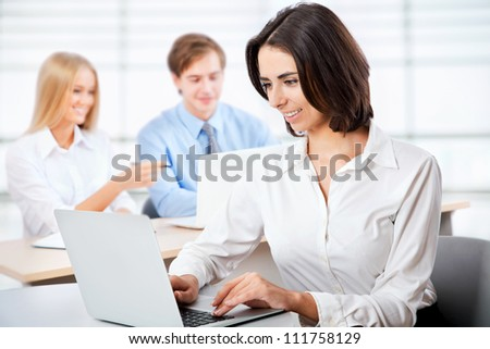 Portrait of a smiling young attractive business woman in a meeting .