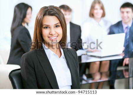 Portrait of a smiling young attractive business woman in a meeting - stock photo
