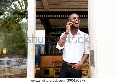 Portrait of a smiling young black businessman talking on mobile phone  - stock photo
