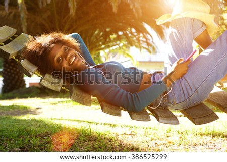 Portrait of a smiling young black woman lying down on hammock listening to music with smart phone - stock photo